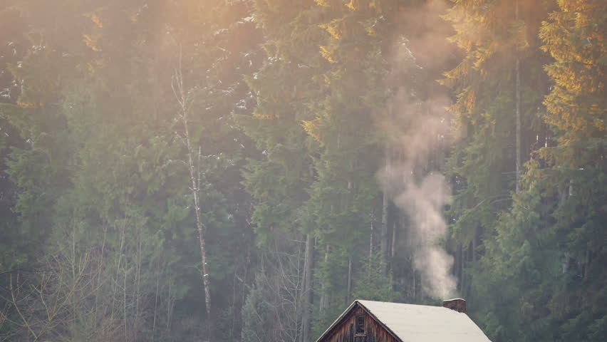 Smoke Rises From Log Cabin In Winter
