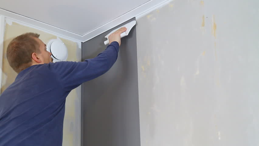 Using a wallpaper tool to remove air behind the wallpaper.