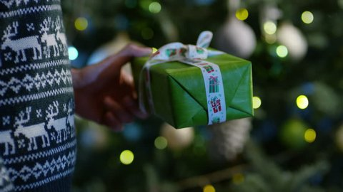 4K  Man holding wrapped gift box near the christmas tree. Shot on RED EPIC Cinema Camera