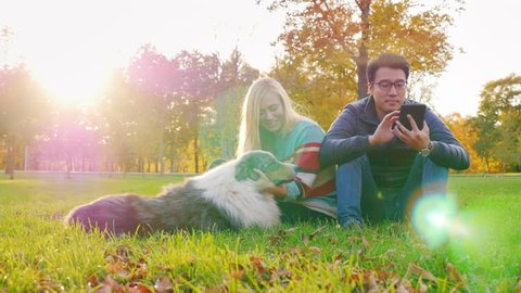 Young multi-ethnic couple relaxing in the park with his dog. Asian man looking into a tablet, caucasian woman playing with the dog