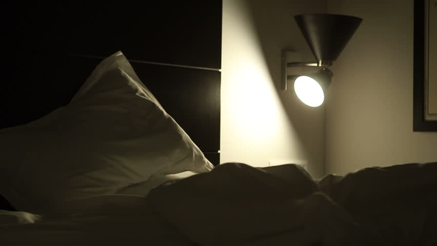 Man lays down in bed and turns off the light in the middle of the night. Man prepares to go to sleep