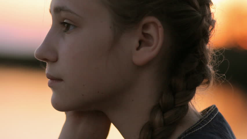 Pensive worried girl hoping - Close up profile portrait of teen girl (14-15) watching sunset or sunrise over calm lake.