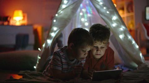Little boys lying in teepee decorated with fairy lights and playing games on tablet in dark room