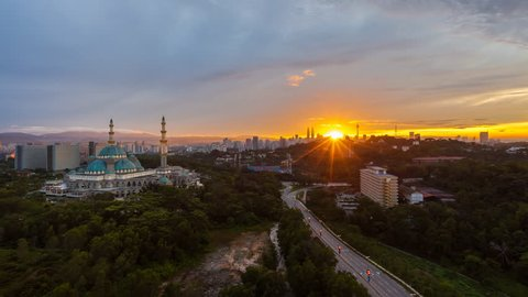Time lapse of The Federal Territory Mosque at sunrise: The mosque's design is a blend of Ottoman and Malay architectural styles, heavily influenced by the Blue Mosque in Istanbul, Turkey. 4K. PAN UP