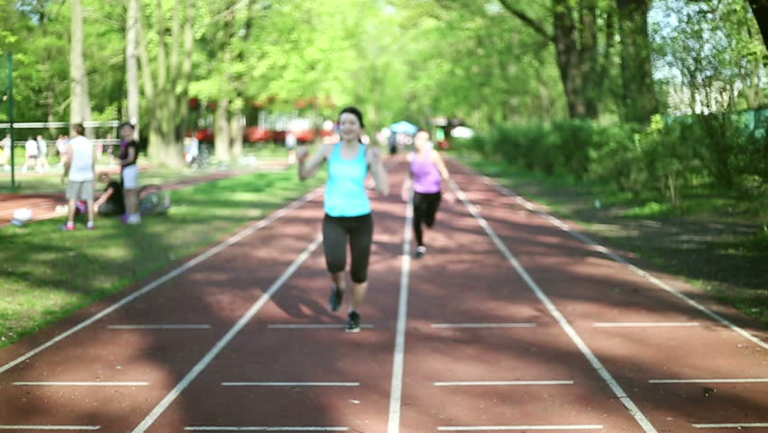 Two young women running on sport track, slow motion
