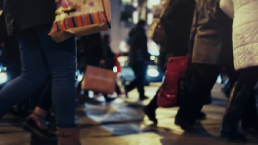 Christmas holiday shoppers at night, cross busy city street,slow motion 100p.Anonymous crowd of pedestrians cross a busy city street on a December night carrying shopping bags.No logos/faces visible | Shutterstock HD Video #22429492