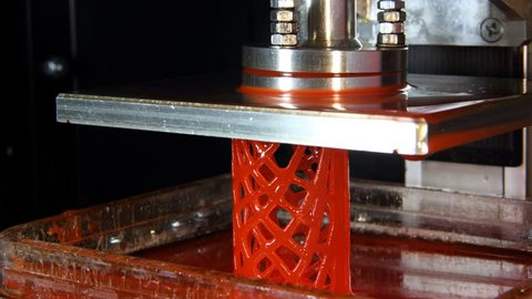 Red lattice bionic cylinder print using DLP machine, additive manufacturing process time lapse. Platform slowly lift up, polymer model created layer by layer, using photo polymerization technique