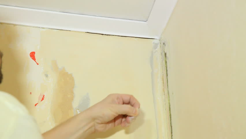 Applying a reinforcement tape in the corner, before spackling and hanging wallpaper.