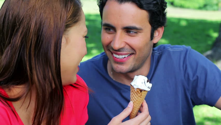 Smiling couple eating ice creams while sitting on the grass in a parkland
