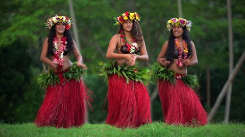 Barefoot Tahitian females in hula skirts and flower headdress performing a traditional dance at celebration ceremony French Polynesia South, Pacific,