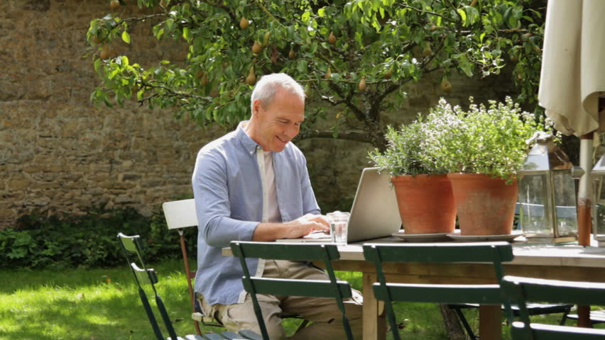 Elegant Wide Shot   Senior Couple At Table In Garden Looking At Laptop Computer  Stock Footage Video 2251357 | Shutterstock