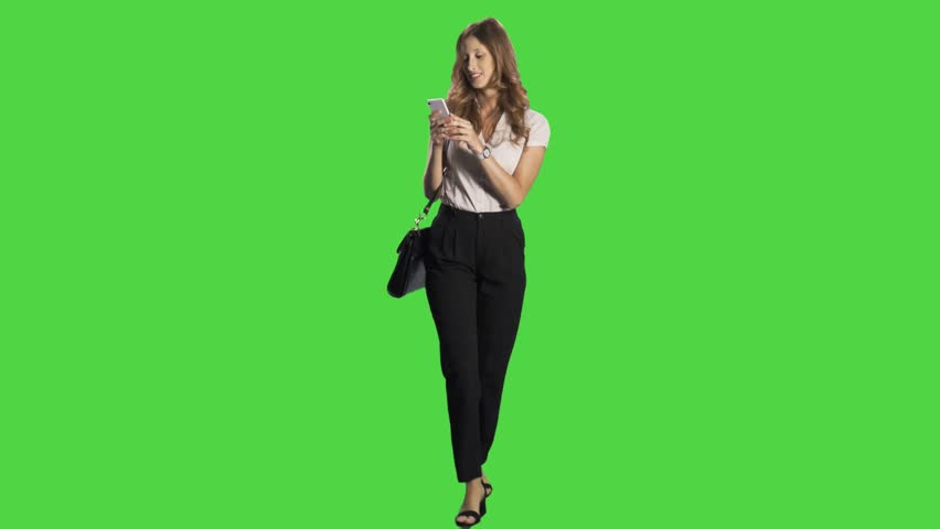 Young business woman walking towards camera, texting happily in a full body shot over a green screen. | Shutterstock HD Video #22514827