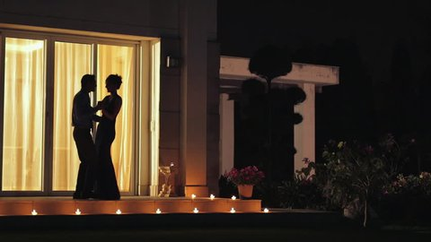 WS Silhouette of couple dancing on patio at night / India