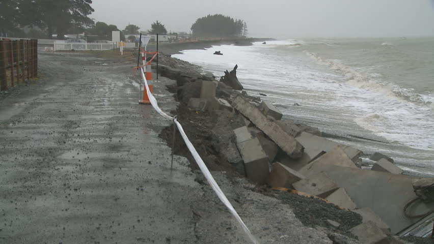 A coastal road sustains sea damage from large storm driven waves