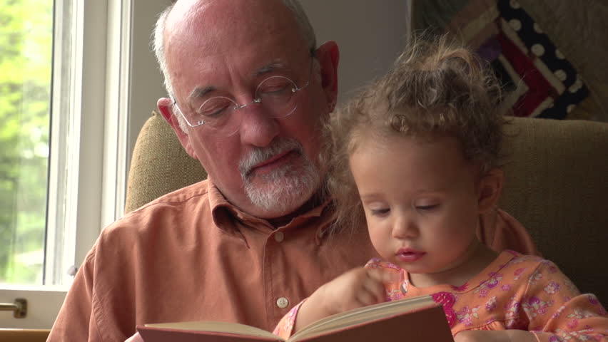 Grandfather reading to his granddaughter