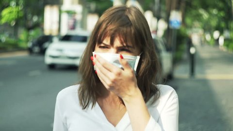 Young woman with mask coughing standing near street in city