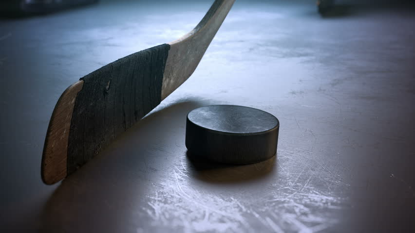 Close-up hockey stick hitting hockey puck in slow motion | Shutterstock Video #22580857