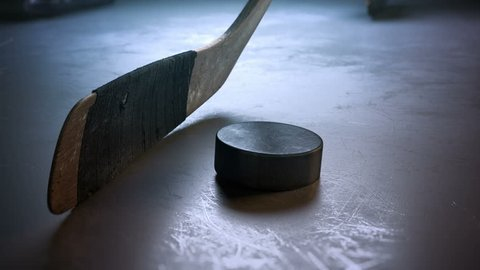Close-up hockey stick hitting hockey puck in slow motion