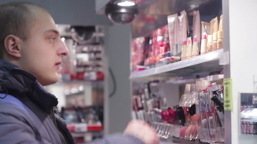 Young man chooses cosmetics in a beauty store, close-up shot. He chooses a gift to girl. | Shutterstock HD Video #22609342