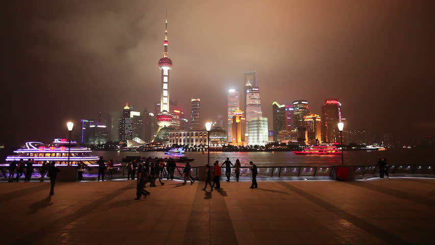 SHANGHAI, CHINA - NOVEMBER 6: Illuminated river boats on the Huangpu River pass the futuristic skyline of Pudong, viewed from the wide promenade of the Bund on November 6, 2011 in Shanghai, China.
