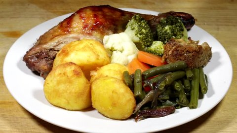 Pouring Gravy Over a Traditional Sunday Family Roast Meal of Roast Duck with Vegetables