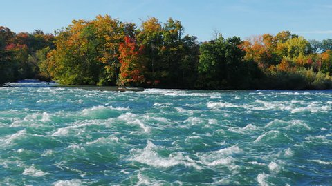 Stormy Niagara River flows to the waterfall. Water foam on the rapids. Slow motion video