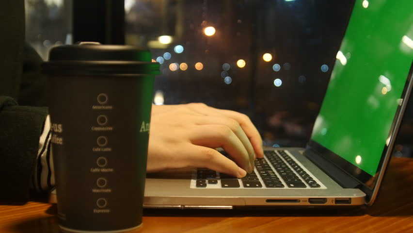 Woman using laptop with green screen in cafe. Woman's hands typing on a laptop keyboard. drink a coffee. | Shutterstock HD Video #22765237