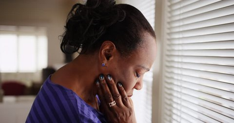 An older black woman mournfully looks out her window. An elderly African American woman sadly looks out her window. 4k