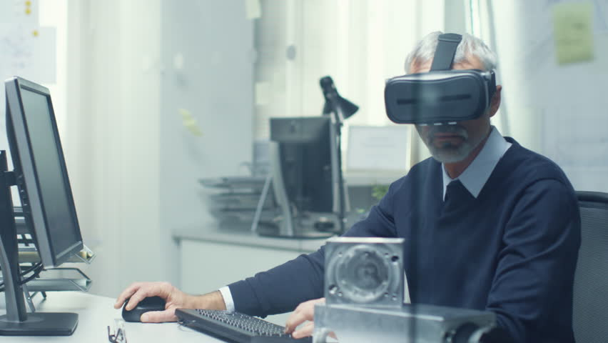 Virtual Reality Engineer Works with VR Glasses On while Simultaneously Doing Programming on His Personal Computer. Shot on RED Cinema Camera in 4K (UHD). | Shutterstock HD Video #22781866