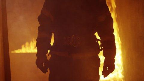Portrait Shot of A Brave Fireman Standing in a Burning Building Fire Raging Behind Him. Open Flames and Smoke in the Background. Shot on RED EPIC 4K (UHD).