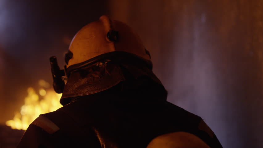 Building is on Fire. Brave Fireman Turns Around and Looks Into the Camera. Tongues of Flame are Licking Walls of the House. Shot on RED EPIC 4K (UHD).