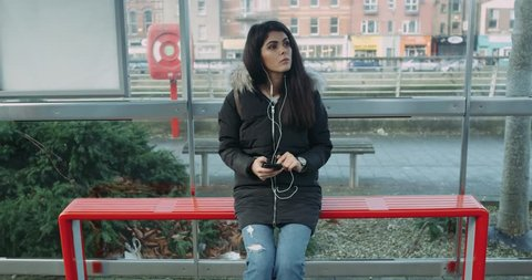 Young woman looking around and waiting for a bus at bus stop. Red Eoic 4k