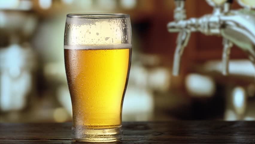 Beer is pouring from the top into the glass. 4K video. | Shutterstock HD Video #22811698