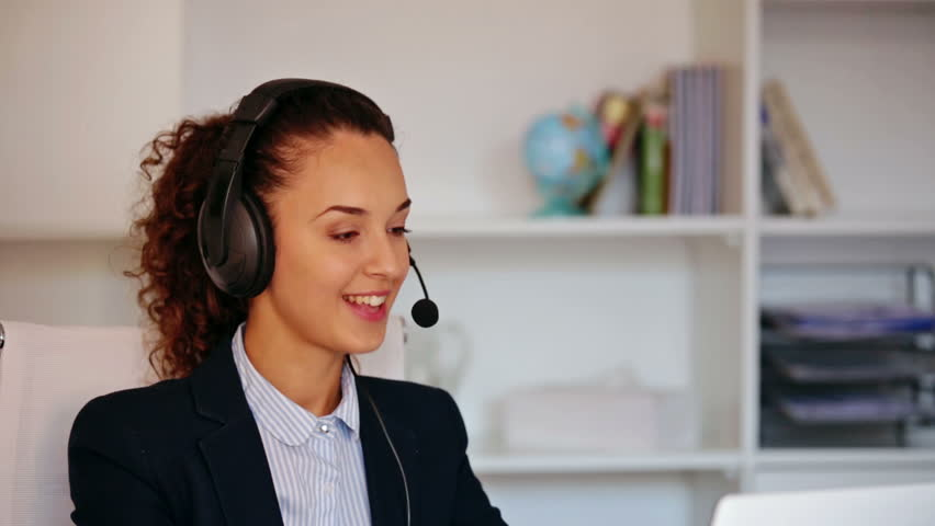 Female receptionist working on computer and talking on the cheerful girl with headset and laptop answering call in office hd stock footage clip sciox Images