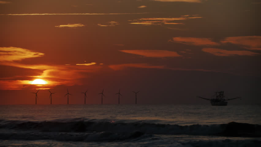 A cinematic shot of offshore windmill wind turbines during a beautiful sunset or sunrise with waves crashing on the beach and a shrimp boat on one side as the red sun bursts through the clouds.