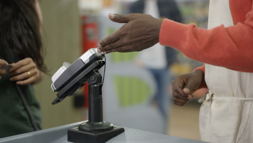 4K Friendly cashier taking payment from a customer at grocery store checkout Dec 2016-UK