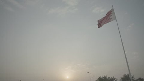 Bahrain Flag. Low-angle view at sunset of a Bahraini flag, high up on a pole, billowing in the breeze.