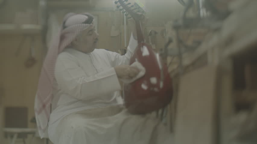 Musical Instruments: Oud Maker, Bahrain. View of a Bahraini oud maker polishing a high shine onto the instrument he made.