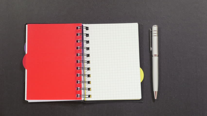 Black dotty spiral notebook with colorful dividers, silver pen on black table, turning over clean white pages. Close up, stop motion, 4K Ultra HD.
