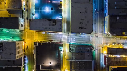Vertical top down aerial view of traffic on streets and intersections at night. 4K UHD timelapse.