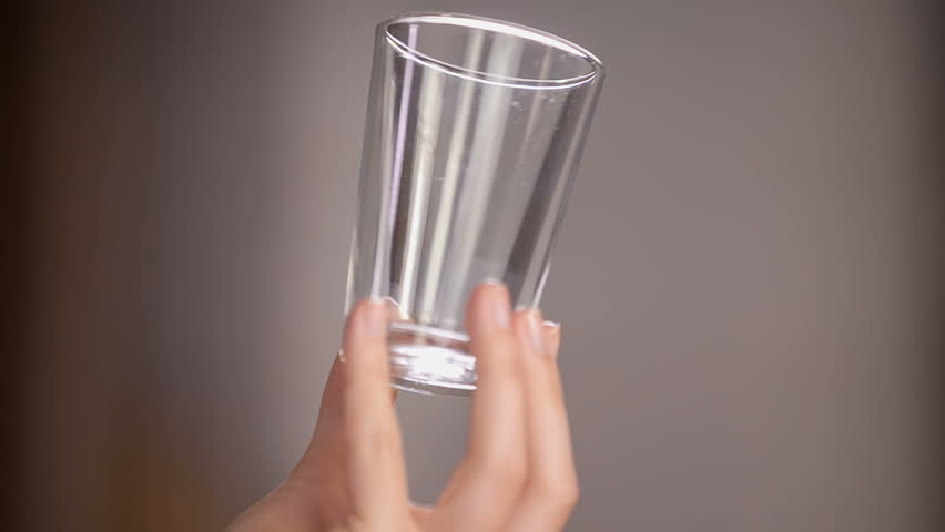 A woman is having an empty glass in her hands and she is checking if the glass is clean. She is looking at it from all sides.