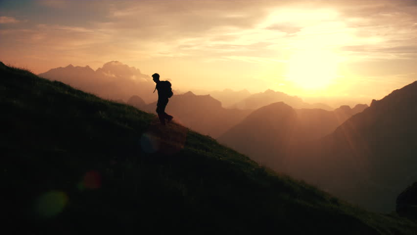 Aerial - Epic shot of a man hiking on the edge of the mountain as a silhouette in beautiful sunset (edited version) | Shutterstock HD Video #22952905