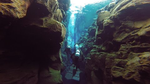 Underwater view of scuba divers going through narrow sections of Silfra, the fissure between 2 tectonic plates in Thingvellir National Park Iceland.