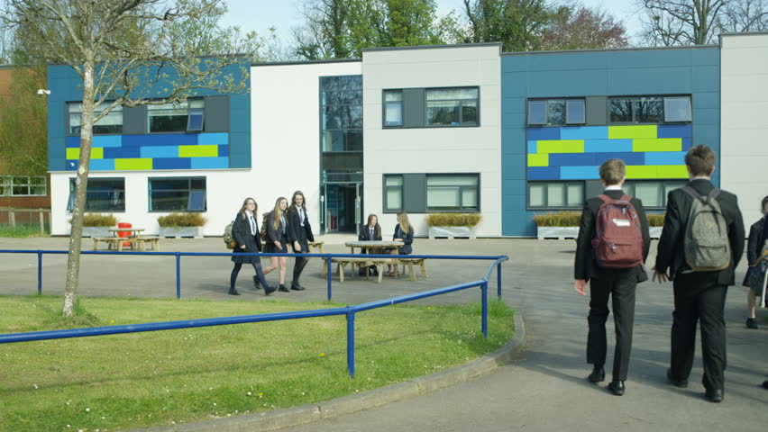 4K Groups of children outside school building, some walking & some sitting down Dec 2016-UK