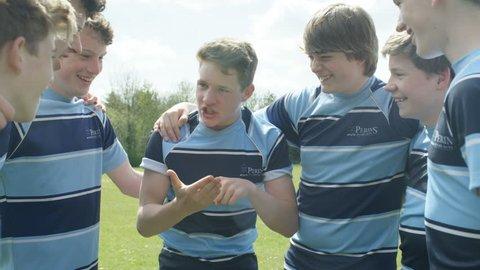 4K Teen boys in a huddle on school sports field having team talk before a game Dec 2016-UK