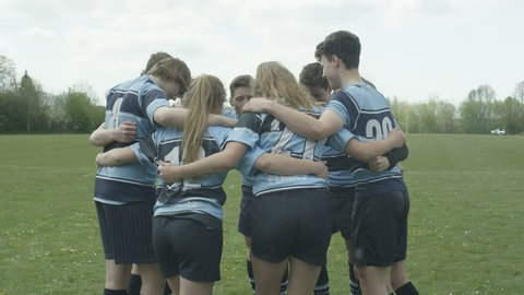 4K Young rugby players (male & female) in a huddle on school sports field Dec 2016-UK