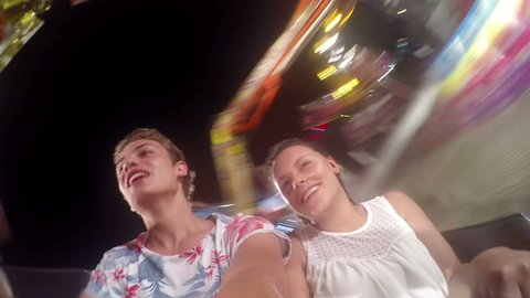 Two teens ride on the Ferris wheel, cheerful and happy adventure
