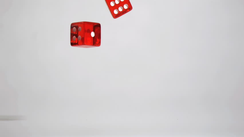 Two red dices in super slow motion turning against a grey background