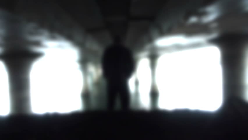 Person walks away, below large freeway bridge in a heavenly effect.