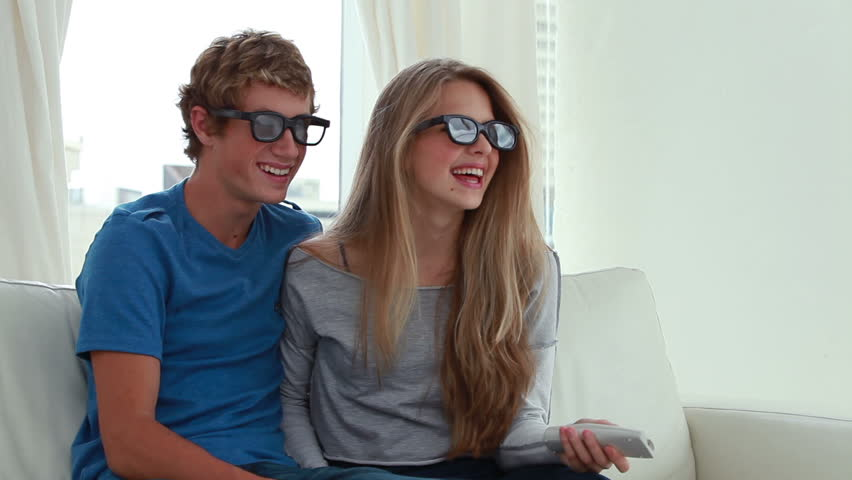 Happy couple wearing 3d glasses in front of the television in the living room